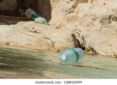 carelessly discarded plastic beverage bottles pollute the beauty of the david stream in ein gedi in israel