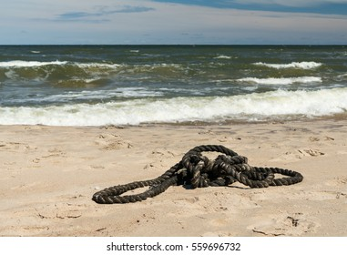 Carelessly thrown rope lies on the sand on the seashore.
