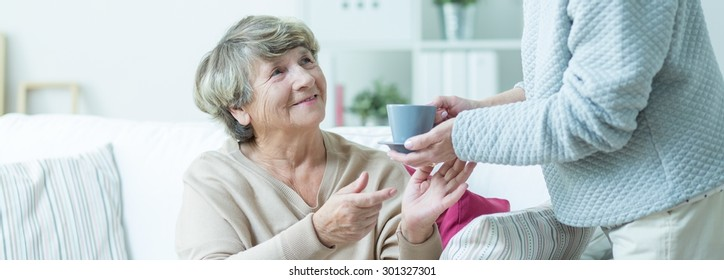 Carer is giving cup of tea to elderly woman
