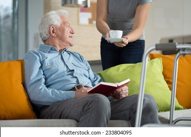 Carer giving disabled man cup of coffee