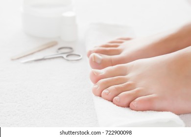Cares about woman's feet nails. Pedicure, manicure beauty salon concept. Scissors and nail file on the white towel.