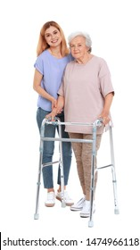 Caretaker helping elderly woman with walking frame on white background