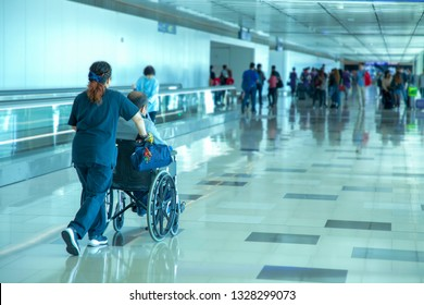 Caretaker pushing elderly people in wheelchair at the airport
