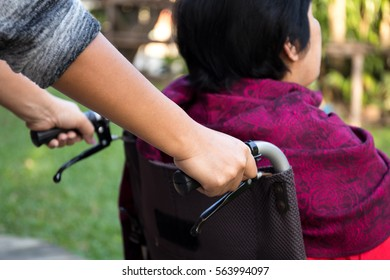 Caretaker pushing senior woman in wheel chair out for fresh air