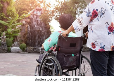 Caretaker spending time in fresh air outdoor with patient in wheelchair