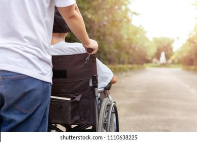 Caretaker spending time outdoor with patient in wheelchair