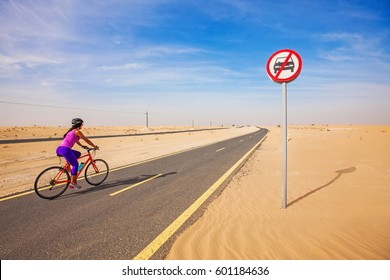 car-free day. woman riding bike on a road in desert