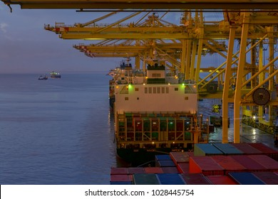 Cargo activities on container cargo terminal of industrial commercial port at sunset.