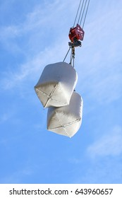 cargo in bags on hook of construction crane on sky background