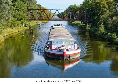 a cargo canal ship passes under an old iron bridge on a sunny autumn day, reflections are to be seen in the water, canal system in the outskirts of Berlin Germany