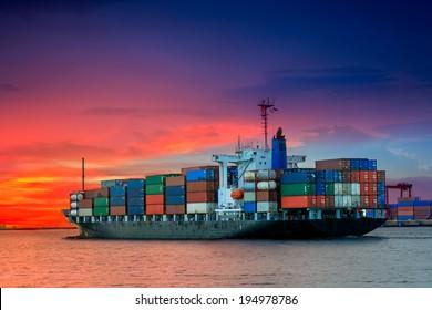 cargo container ship at mediterranean coast in sunset