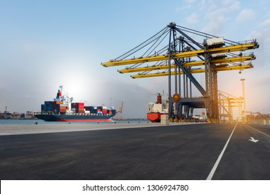 cargo crane in the international yard port for loading big tank from ship to truck concept logistic shipping by sea , logistic service and transportation..