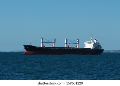 Cargo freight ship on calm water against blue sky