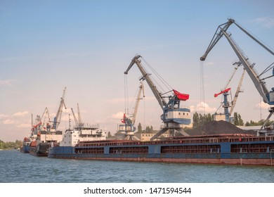 Cargo port , barges are for loading coal. Portal cranes , ship's queue for loading. Russian river cargo port.