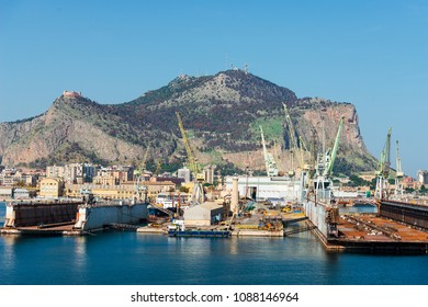 Cargo port of Palermo on the Mediterranean coast with buildings and port cranes on the coast against the background of the Sicilian mountains