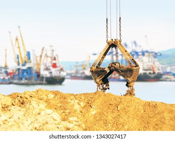 Cargo sea port, work. Unloading sand. Grapple lifting device for port cranes for bulk materials, iron scoop