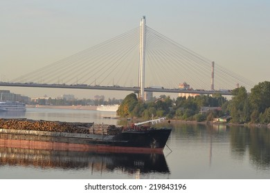 Cargo ship and cable-braced bridge at evening, outskirts of St. Petersburg, Russia.