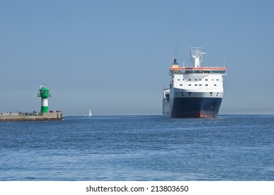 Cargo ship crossed the mole with the small lighthouse in Travemuende