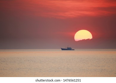 A cargo ship in the dea with the bigsunset