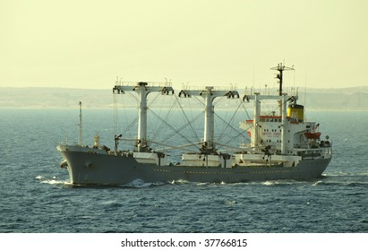 Cargo ship designed for transporting of bulk cargo, making turn on the sea surface