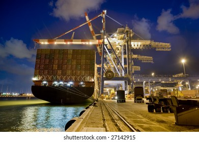 cargo ship at dock by night from behind