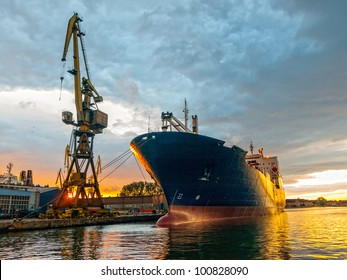 Cargo ship in the harbor at sunset. Gdansk, Poland.