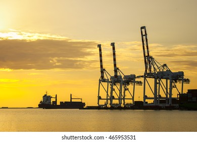 Cargo ship loaded the container in the shipping container terminal in sunset.