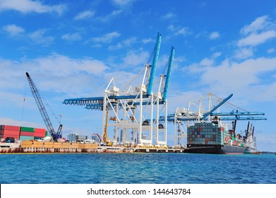Cargo ship at Miami harbor with crane and blue sky over sea.