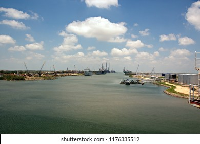 Cargo ship movement to the outlet via the shipping channel of the port of Brownsville, USA. A view of the coastline, berths and old of rusty ships, warships decommissioned for scrap.July 2018.