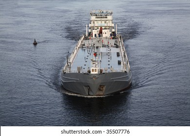 The cargo ship moves on the river