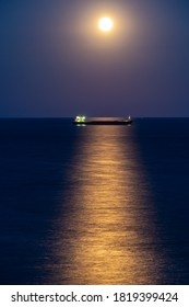 Cargo ship at night with full moon over the horizon