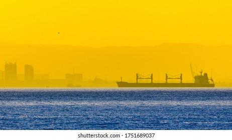 Cargo ship on the background of Novorossiysk at sunset