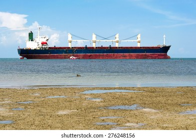 Cargo ship on the blue sea under white cloud sky