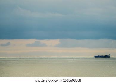 Cargo ship on horizon at sunset