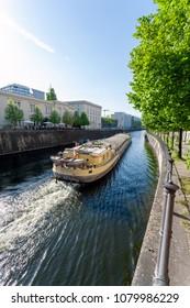 Cargo ship on a river through a city (Berlin)
