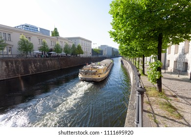 Cargo ship on a river through downtown area of a city, on a sunny spring day- Berlin 2018