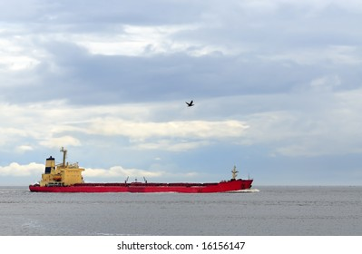 Cargo ship in open sea under cloudy blue sky