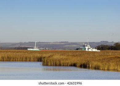 a cargo ship passing reed beds on its way up the river ouse to the port of goole in east yorkshire