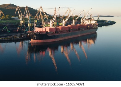 The Cargo Ship is in the Port Pier at the Loading of Coal at Sunset. Aerial View from Drone. Location Kandalaksha Town, Cola Peninsula, Russia