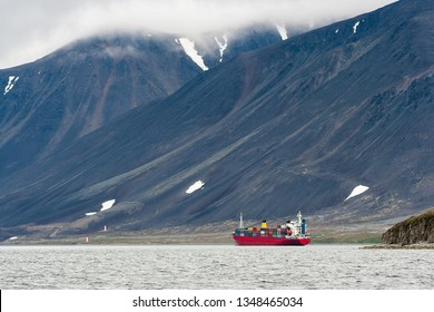 Cargo ship in Providence Bay. Delivery of goods to the Arctic. Development of the Northern Sea Route. Beautiful mountains on the coast of the Bering Sea. Chukotka, Far East of Russia. Extreme North.