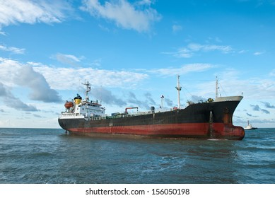 Cargo ship run aground on rocky shore waiting for rescue