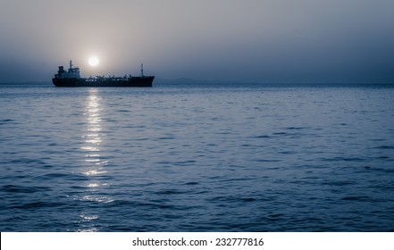 Cargo ship sailing with full moon rising above it