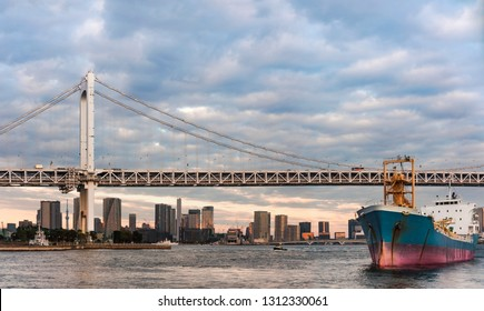 Cargo ship sailing in Odaiba Bay under the Rainbow Bridge of Odaiba bay in Tokyo.