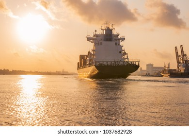 Cargo ship is sailing out of the harbor at evening to sea to transport cargo in the container.Logistics and transportation of International, Freight Transportation, Shipping
