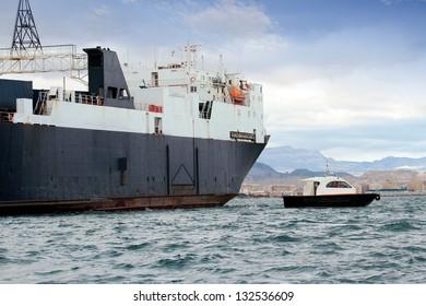 Cargo ship sailing with pilot cutter