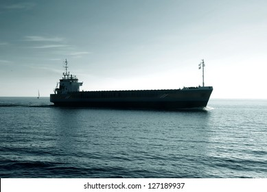 cargo ship sailing in still water heading for the port