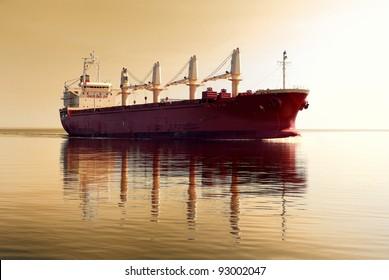 cargo ship sailing in still water near port of Riga