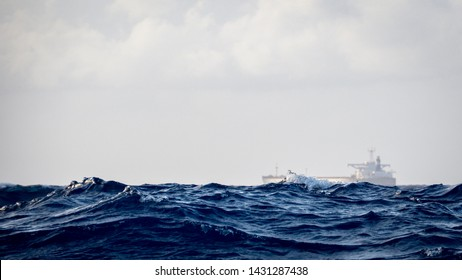 Cargo ship, sea freighter sailing in the middle of the ocean with big waves.  Concept of maritime industry transportation, import and export international and commercial nautical shipping.