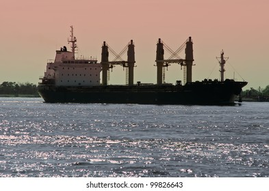 Cargo ship in silhouette on river