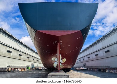 Cargo ship stern moored in floating dry dock propeller center of rudder, slipper wood, Big ship rear view under Repair, maintenance already in shipyard Thailand